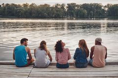 Carefree time with friends. Rear view of young people in casual wear talking while sitting on the pier royalty free stock photos