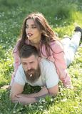 Carefree time together. Couple in love on sunny outdoor. Woman lying on man with flowers in mouths. Couple relax on. Carefree time together. Couple in love on stock photos