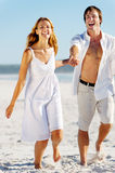 Carefree walking beach couple Stock Photography