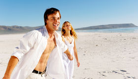 Carefree walking beach couple stock photography