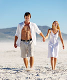 Carefree walking beach couple stock images