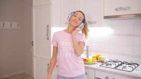 Carefree weekend morning, woman dancing listening to music at home in slow motion stock footage