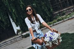 Carefree wheeling. Attractive young woman in casual wear smiling while cycling outdoors Royalty Free Stock Image