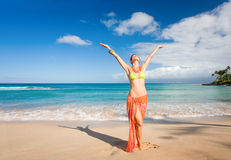 Carefree woman. With orange sarong on beach with turquoise waters Stock Photography