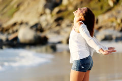 Carefree woman. Stands with her hands out embracing the sunshine at the beach Royalty Free Stock Images