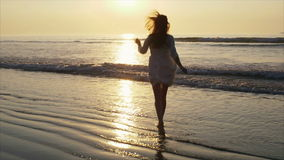 Carefree woman in barefeet running towards sea during sunset. Rear view slow motion footage of barefoot woman running towards sea during sunset. Full length of stock footage