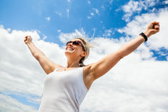 Carefree woman. Beautiful mid 30s carefree woman with arms outstretched against a blue sky on a sunny day royalty free stock photos