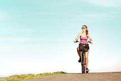 Carefree woman with bicycle riding on road  having. Young woman on the bicycle riding on road having fun and smiling Royalty Free Stock Photo
