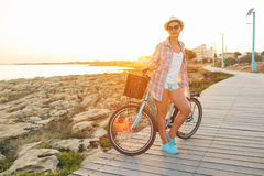 Carefree woman with bicycle riding on a wooden path at the sea, Stock Photo