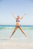 Carefree woman in bikini jumping on the beach Stock Image