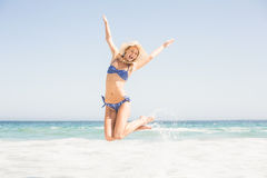 Carefree woman in bikini jumping on the beach Stock Photos
