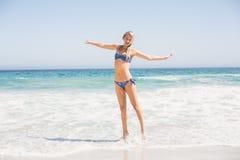 Carefree woman in bikini standing on the beach Stock Photos