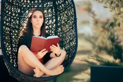 Summer Girl Reading a Novel Outdoors in Nest Chair Royalty Free Stock Photography