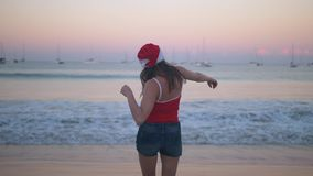Carefree woman dancing and jumping happy in santa hat and red swimsuit at sunset on the tropical paradise beach stock video footage