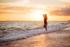 Carefree woman dancing in the sunset on the beach. royalty free stock images