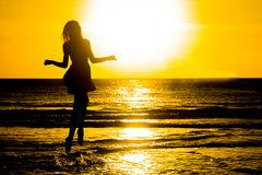Carefree woman dancing in the sunset on the beach. vacation vita Stock Photos