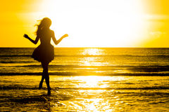 Carefree woman dancing in the sunset on the beach. vacation vita Royalty Free Stock Photo