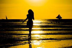 Carefree woman dancing in the sunset on the beach. vacation vita Royalty Free Stock Images