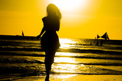 Carefree woman dancing in the sunset on the beach. vacation vita Royalty Free Stock Photos