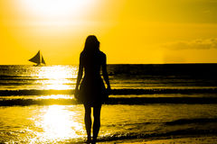 Carefree woman dancing in the sunset on the beach. vacation vita Stock Photography