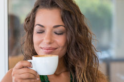 Carefree Woman Drinking Capuccino Stock Photography