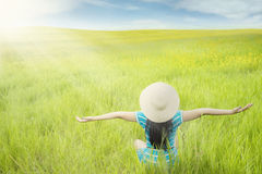 Carefree woman enjoy green meadow view. Rear view of happy woman sitting on the meadow while wearing hat and enjoy beautiful landscape with green meadow view Stock Photos