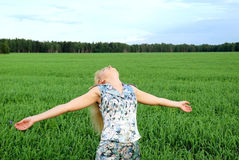 Carefree woman in green field. Carefree young woman in green countryside field with arms outstretched looking upwards Royalty Free Stock Photography