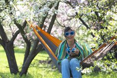 Carefree woman with her funny dog. Dachshund, in carnival glasses is relaxing in a hammock on the green meadow under a wild blooming cherry, having fun on a Royalty Free Stock Images
