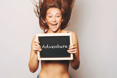 Carefree woman holding a chalkboard saying adventure. Royalty Free Stock Photo