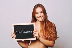 Carefree woman holding a chalkboard saying confidence Royalty Free Stock Photography