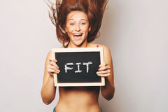 Carefree woman holding a chalkboard saying fit. Stock Image