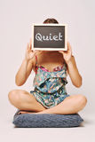 Carefree woman holding a chalkboard saying quiet Royalty Free Stock Photo