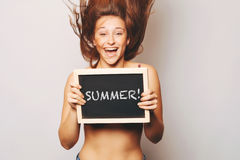 Carefree woman holding a chalkboard saying summer. Royalty Free Stock Image