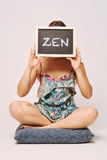 Carefree woman holding a chalkboard saying zen. Stock Image