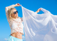 Carefree woman holding white fabric in wind Stock Photography