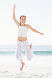 Carefree woman in jumping on the beach Stock Photos