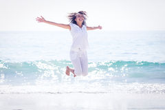 Carefree woman jumping on the beach Stock Image
