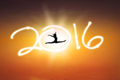 Carefree woman jumps with numbers 2016. Silhouette of carefree young woman jumping on the sky with numbers 2016 enjoy new year holiday Royalty Free Stock Image