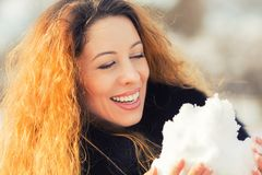Carefree woman with long curly hair playing with snow in park Stock Photo