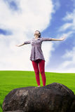 Carefree woman in meadow. Young girl spreading hands with joy and inspiration facing the sky Royalty Free Stock Images