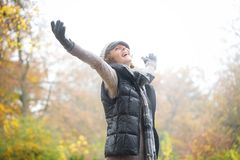 Carefree Woman with Outstreched Arms in Autumn. A carefree woman with outstretched arms welcoming winter during autumn. She is smiling and wearing warm clothes Stock Image