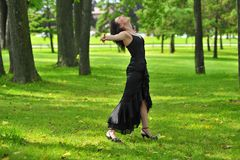 Carefree woman in park. Carefree young woman with outstretched arms in summery park Stock Photography