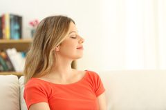 Woman relaxing with closed eyes at home. Carefree woman relaxing with closed eyes sitting on a sofa in the living room at home stock photography
