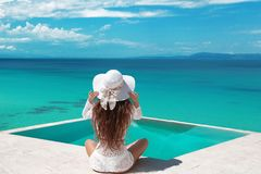 Carefree Woman relaxing in infinity swimming pool looking at vie. W. Luxury resort. Beautiful destination summer vactions. Back view of traveller girl in beach royalty free stock photography