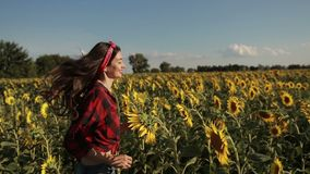 Carefree woman running through field of sunflowers stock video footage