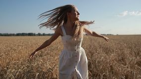 Carefree woman running through golden wheat field stock footage