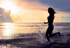 Carefree woman running in the sunset on the beach. vacation vitality healthy living concept. water drops Stock Image