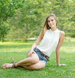 Carefree woman sitting in a green field Royalty Free Stock Images