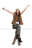 Carefree Woman Sitting On A Top With Arms Outstretched Stock Image