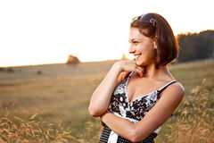 Carefree woman smiling. On meadow at sunset Stock Image
